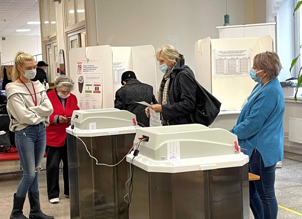 Cử tri bỏ phiếu vào thùng phiếu điện tử dưới sự giám sát của 2 nhân viên tại điểm bầu cử