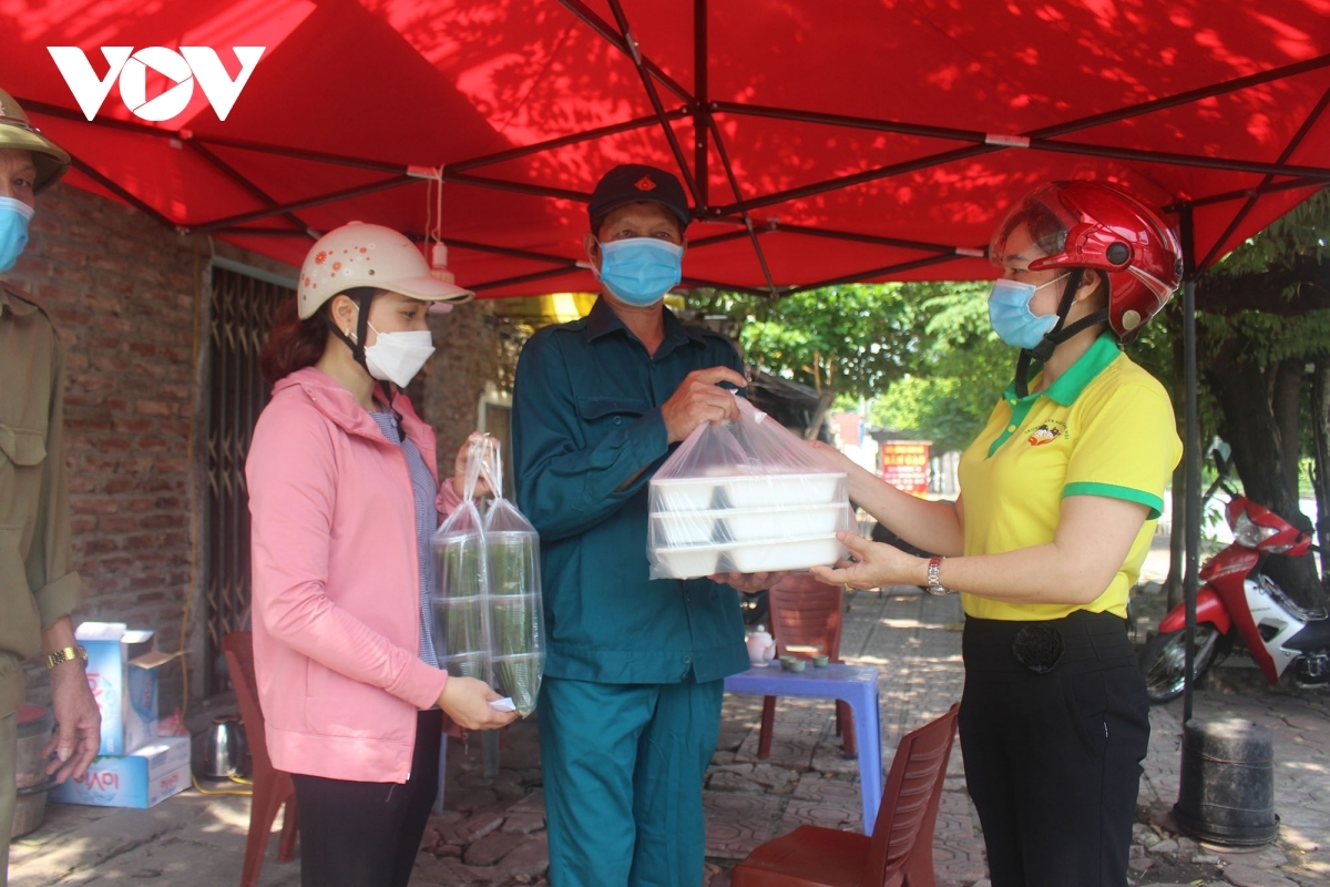 A haul of free meals are handed over to frontline workers at a COVID-19 checkpoint located in Ha Dong district.