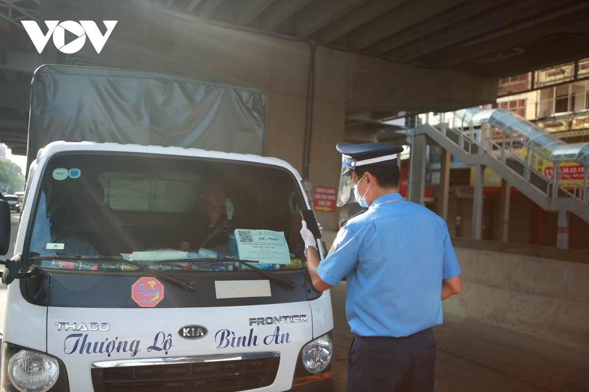 A policeman scans a QR code to check the healthcare status of commuters.