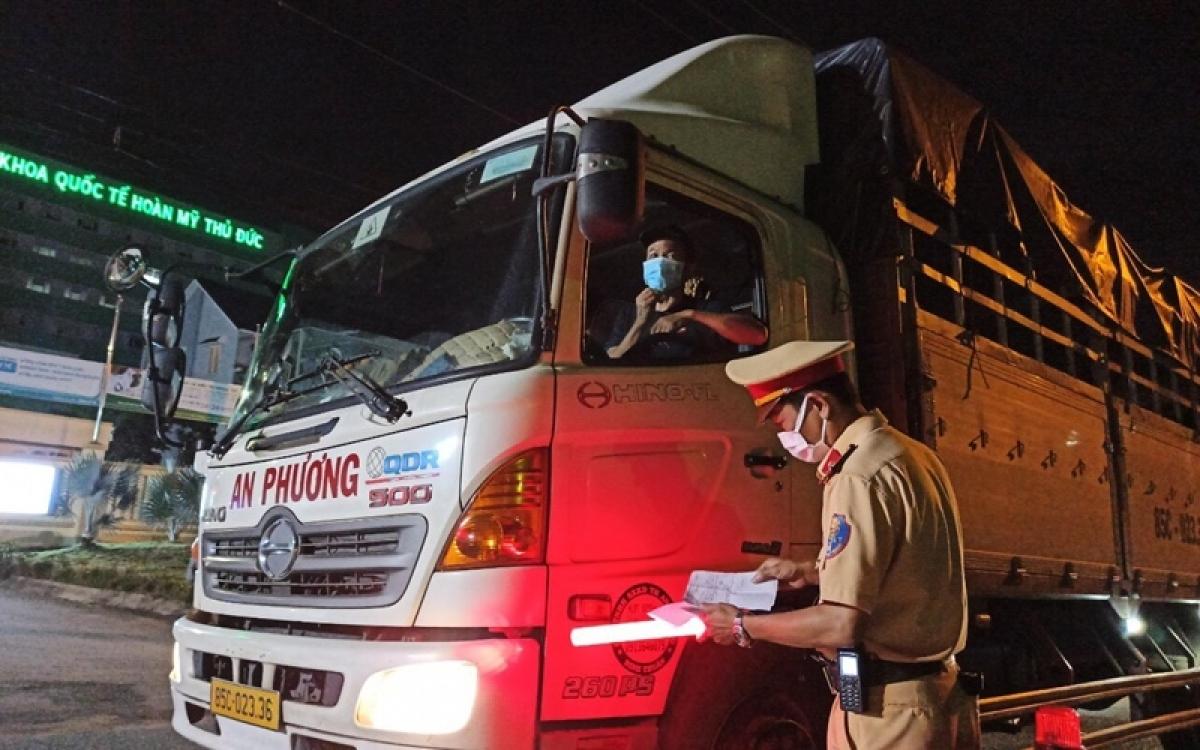 Lực lượng chức năng kiểm tra xe vận chuyển hàng hóa tại một chốt kiểm soát dịch COVID-19.