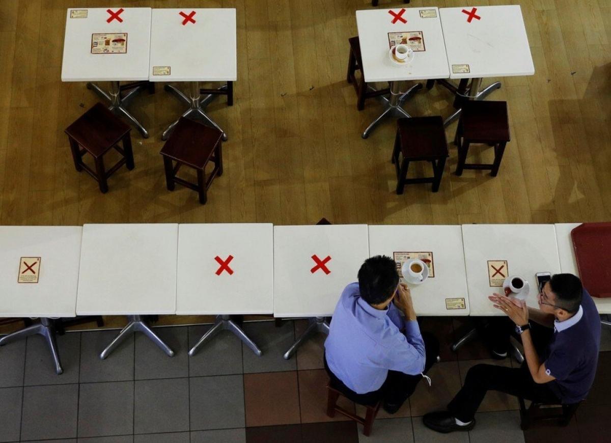 Những chiếc bàn được đánh dấu để thực hiện giãn cách tại một quán café ở Singapore. Ảnh: Reuters