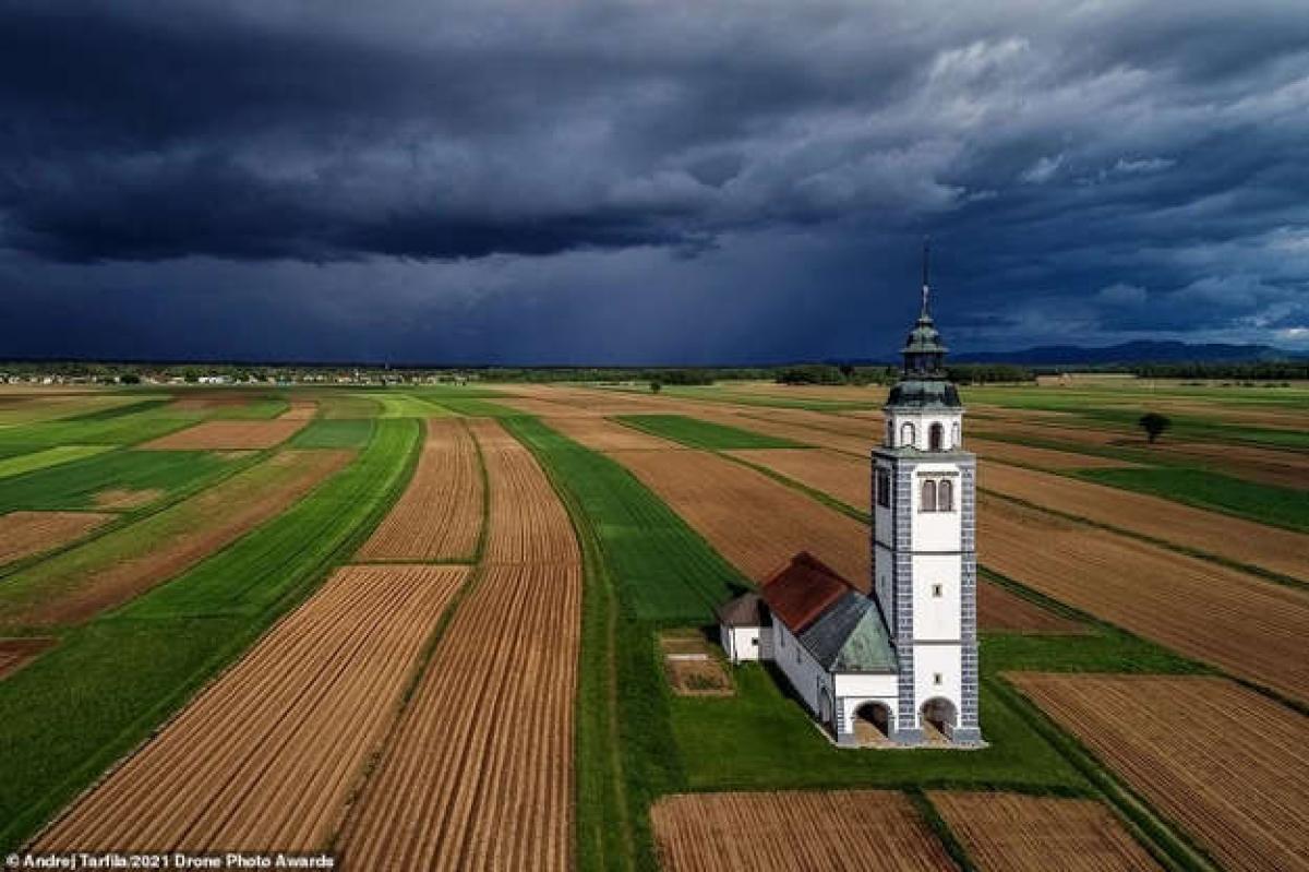 Bức ảnh ấn tượng thuộc hạng mục Đô thị của nhiếp ảnh gia Andrej Tarfila cho thấy nhà thờ Saint Ursula nằm giữa cánh đồng ở thành phố Kranj, Slovenia khi một cơn bão mùa xuân chuẩn bị đến.