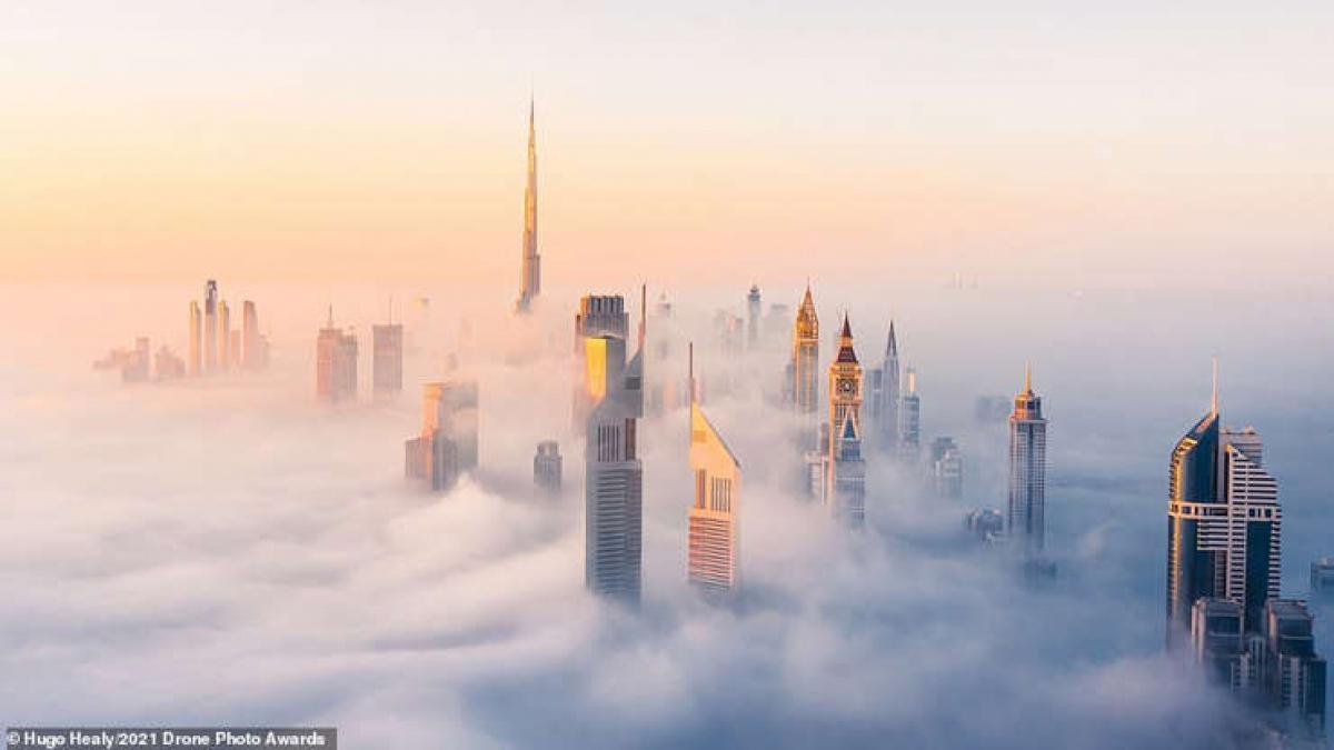 """Một sáng sương mù ở Dubai trong bức ảnh ấn tượng của nhiếp ảnh gia Hugo Healy với chủ đề Đô thị. Nhiếp ảnh gia này chia sẻ, các điều kiện đã """"tạo nên bối cảnh hoàn hảo cho một bức ảnh từ trên cao"""" với những tòa nhà chọc trời vượt lên những đám mây và tạo nên cảnh tượng giống như một thành phố đang trôi trên bầu trời."""