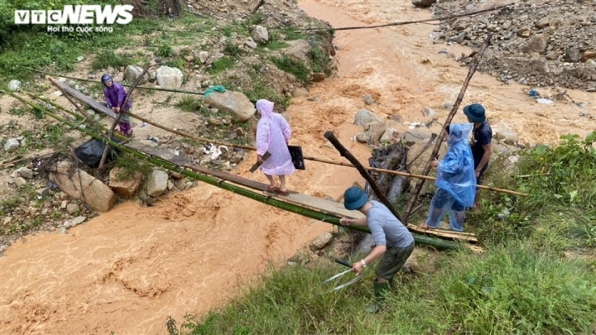 In the mountainous district of Phuoc Son in Quang Nam province, heavy rain results in difficulties for local people as they attempt to travel.