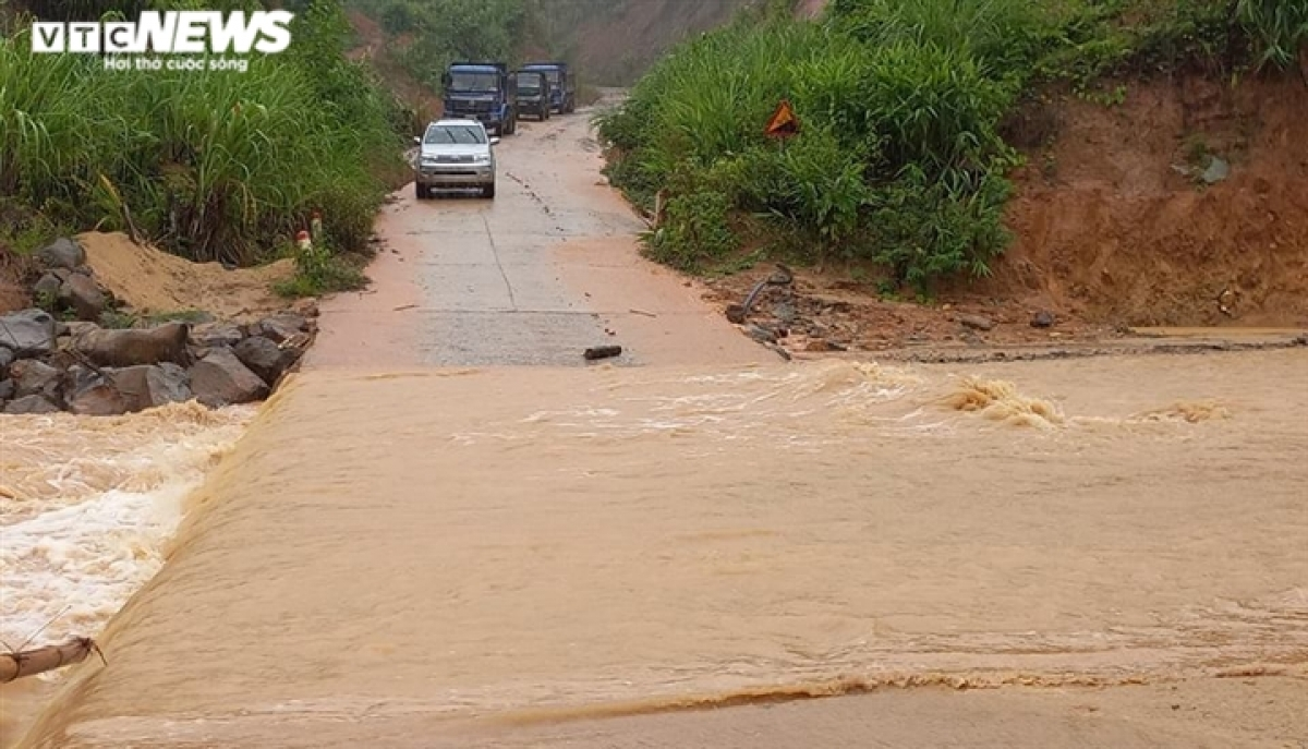 Many cars in Phuoc Thanh commune are unable to move due to the strong flow of water in front of them.