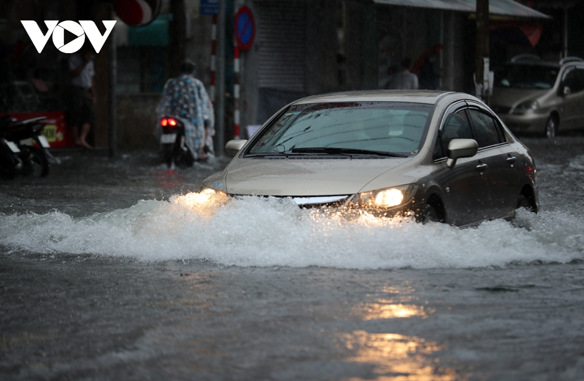 A car driver tries to navigate through the deluged on Ham Nghi street.