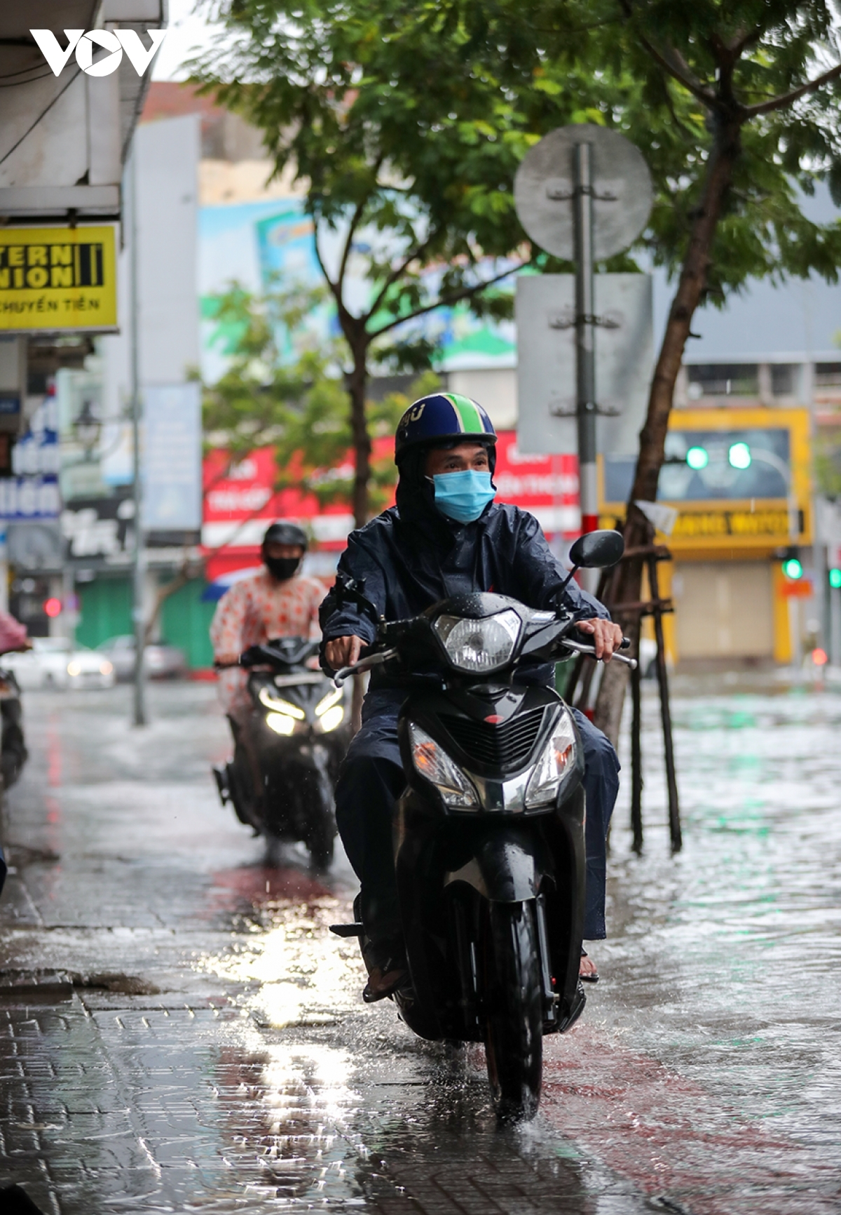 A number of motorbike drivers are forced to travel on the pavements as Le Duan street is left flooded.