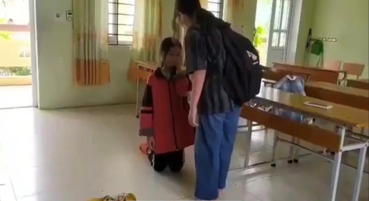 Nữ sinh áo đen bắt nữ sinh áo đỏ quỳ xuống trong lớp học, văng tục chửi thề, tát liên tiếp vào mặt bạn học. (Ảnh cắt từ clip)
