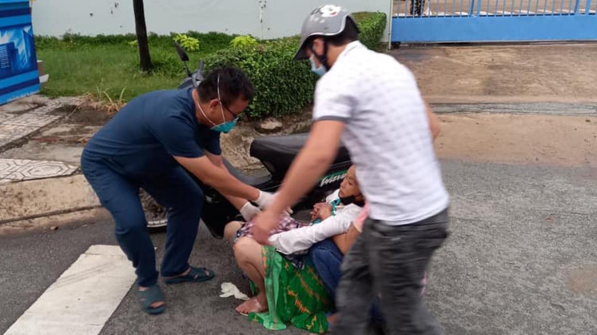 Bác sĩ Huỳnh Minh Chín (bên trái) đỡ đẻ thành công cho sản phụ ngay bên lề đường.