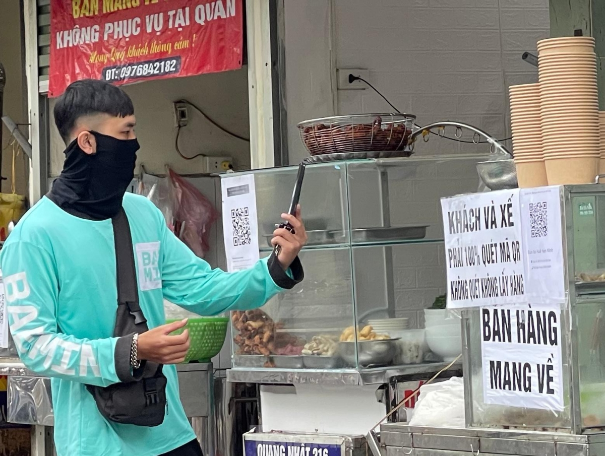 A shipper scans a QR code before making a purchase in an eatery on Doi Can street in Ba Dinh district.