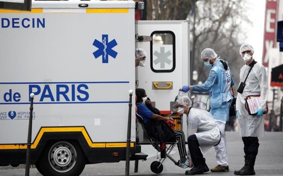 Nhân viên cấp cứu di chuyển bệnh nhân bị nghi mắc Covid-19 từ nhà đến bệnh viện ở Paris, Pháp, ngày 20/3. (Ảnh: Reuters)
