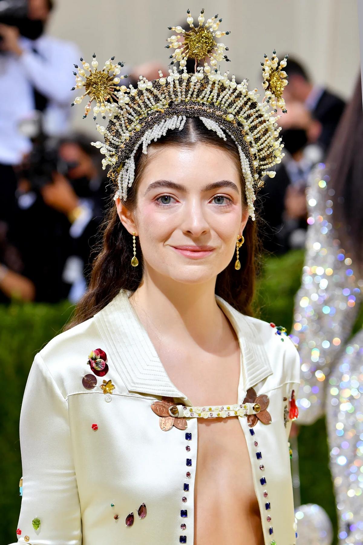 Lorde gây ấn tượng với vương miện đính họa tiết ba chùm tia nắng mặt trời.