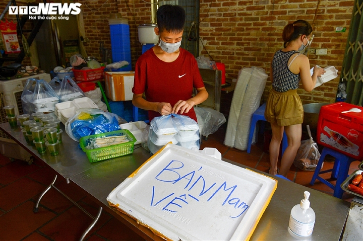Workers are busy packaging sets of meals for take-away services.