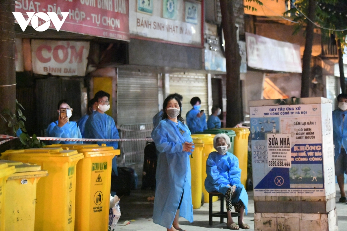 Local people in protective clothing voice their support for the measure in order to bring the outbreak under control.