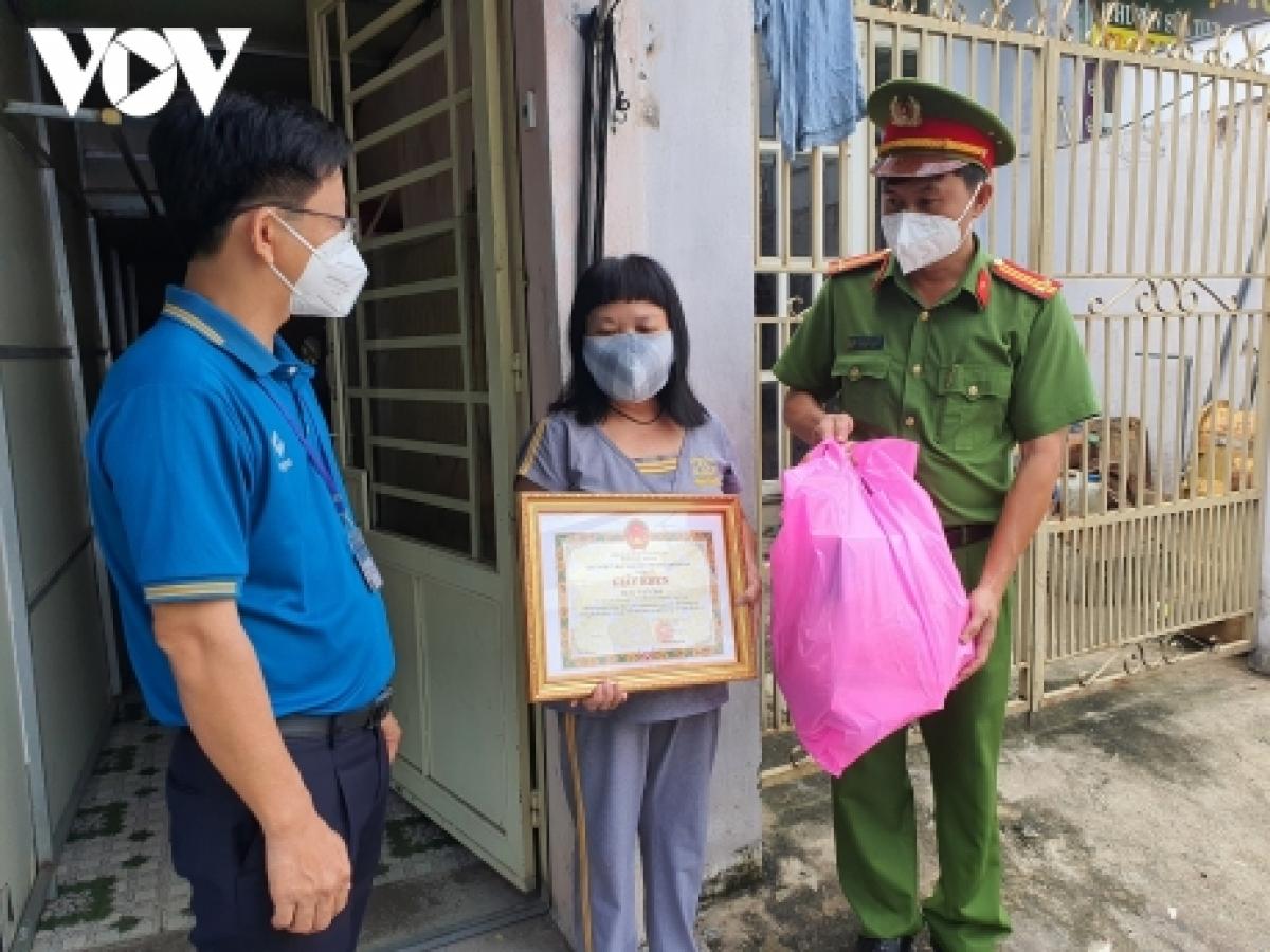 Lãnh đạo Công an TP. Thủ Đức và UBND phường Linh Trung tặng giấy khen và quà cho hộ bà Lê Tuyết Mai.