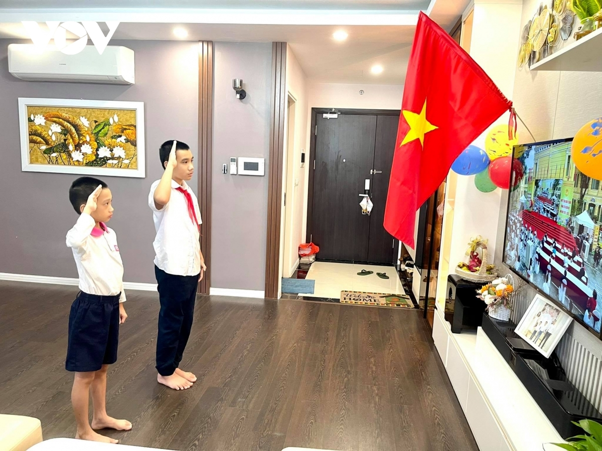 Học sinh tiểu học Hà Nội đứng nghiêm chào cờ trước màn hình tivi trong lễ khai giảng năm học 2021-2022 sáng 5/9.