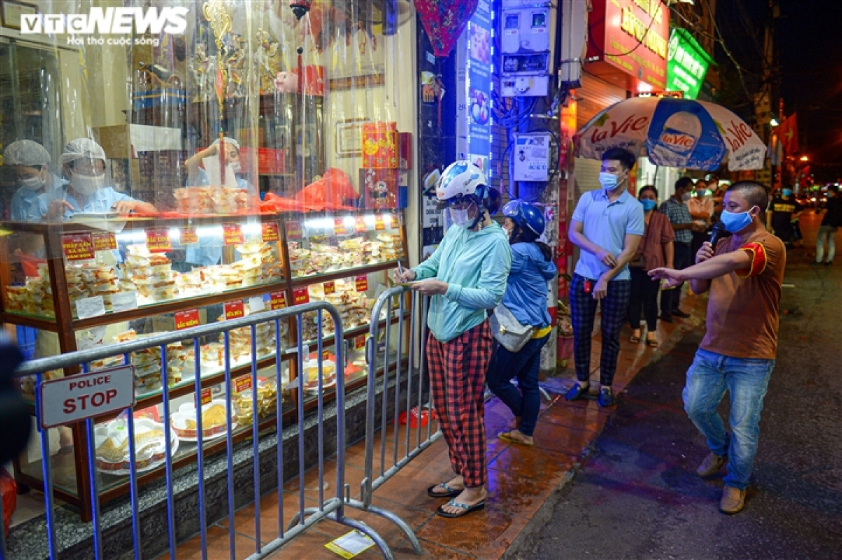 An increasing number of people flock to Xuan Dinh village in the evening as security forces continuously remind traders of the need to maintain a safe distance for the ongoing COVID-19 fight.
