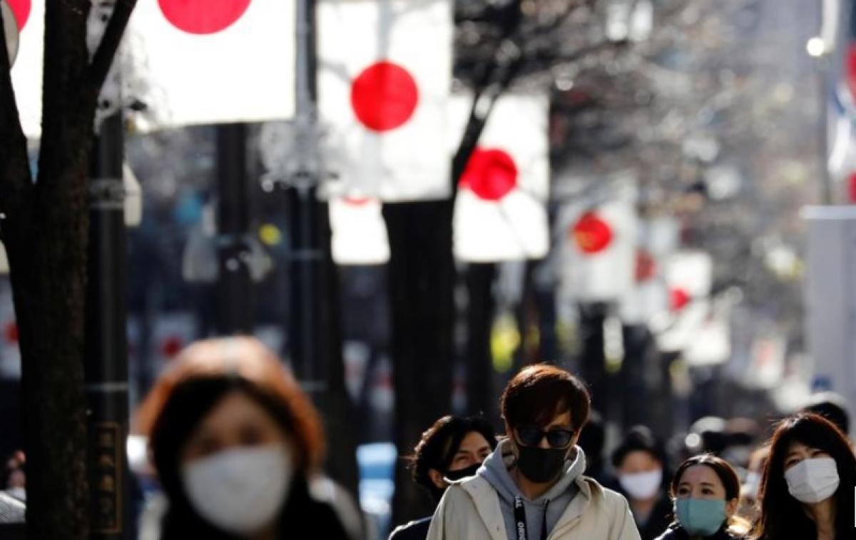 Người Nhật Bản ở Tokyo đi bộ đeo khẩu trang bảo vệ. Ảnh: Reuters.