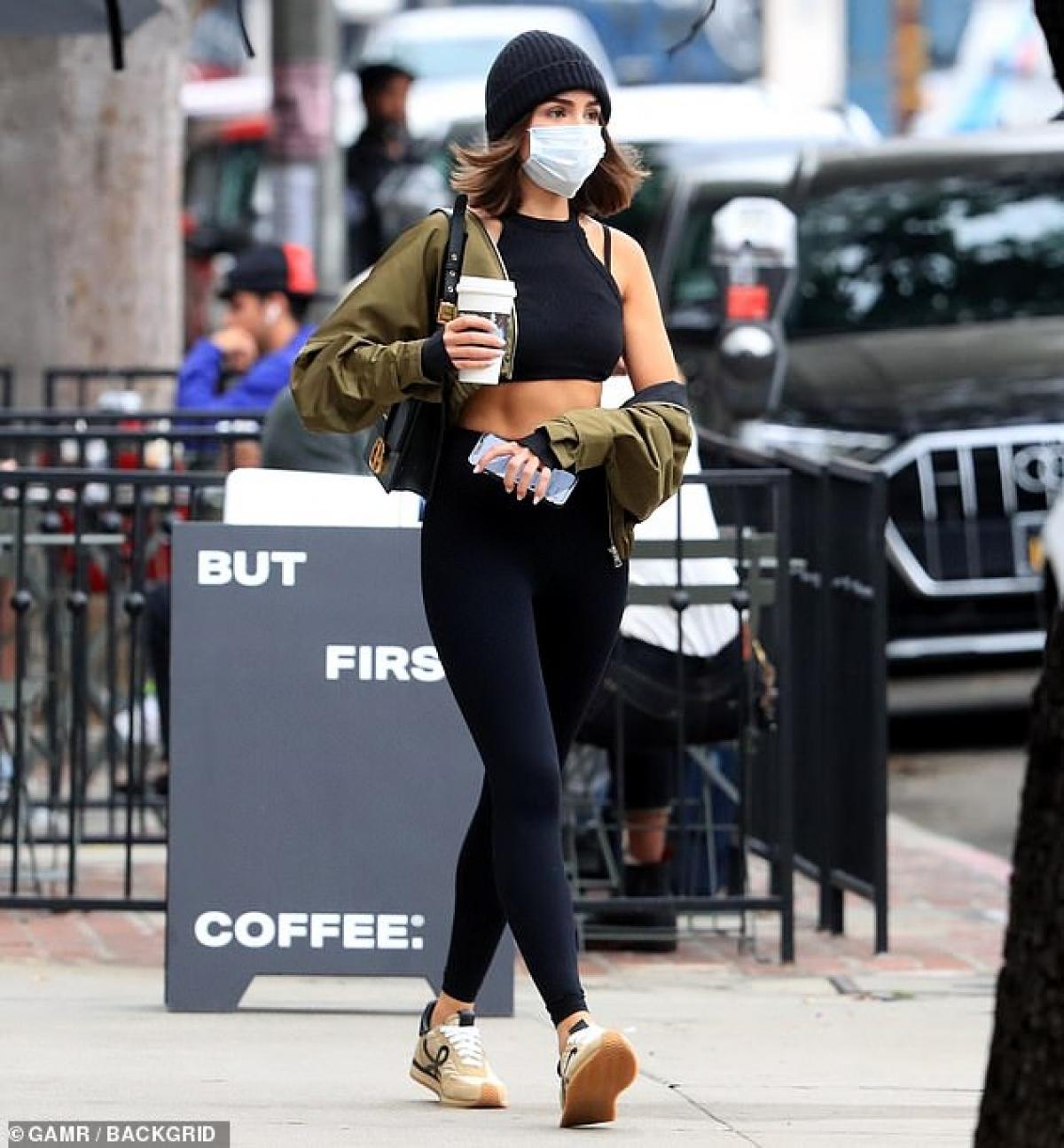 Người đẹp cắt tóc trẻ trung, vừa đi vừa thưởng thức cafe ngay trên phố.