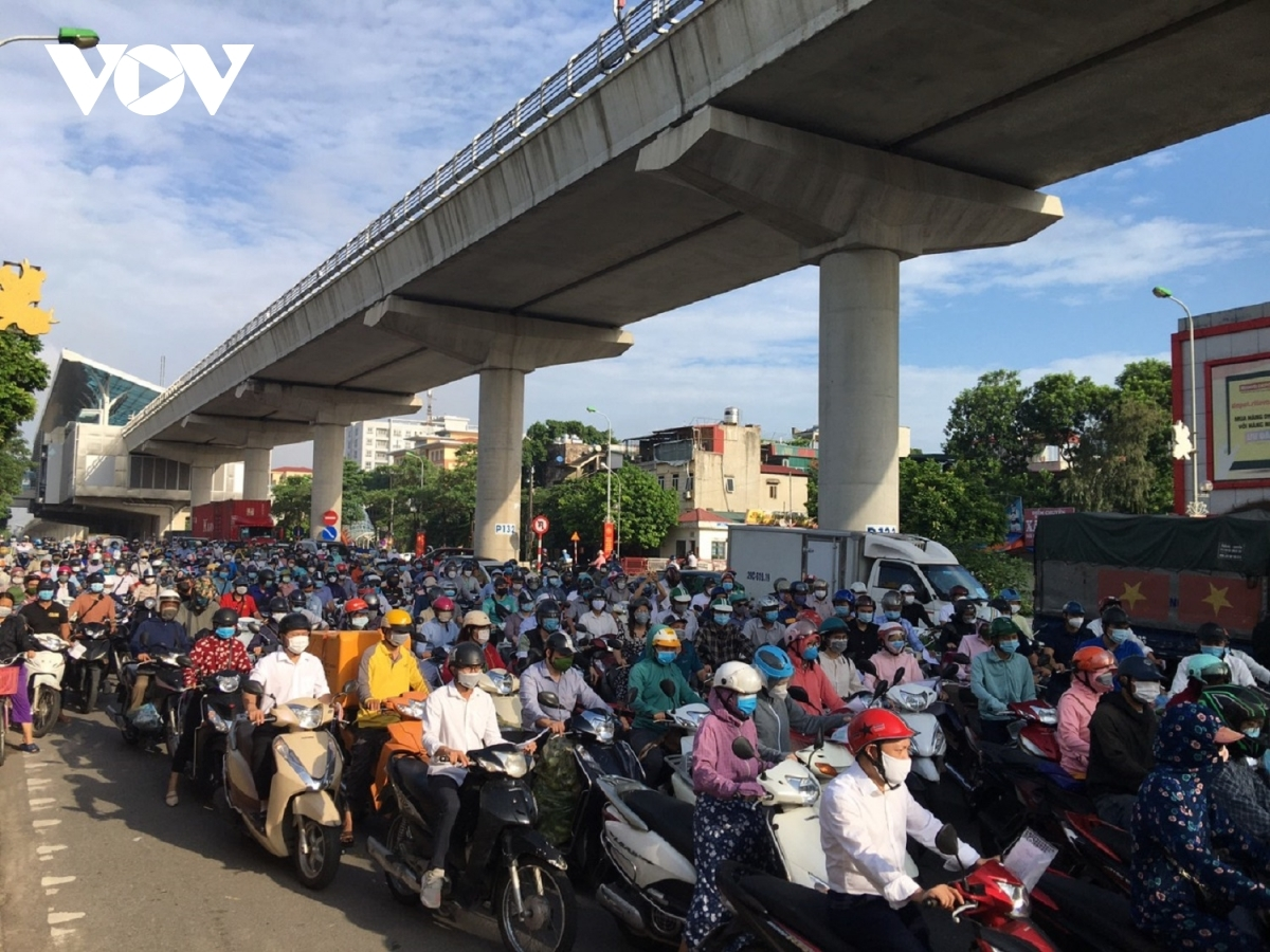 Crowds of vehicles and people can be seen at a COVID-19 checkpoint on Cau Dien road leading to the city centre.