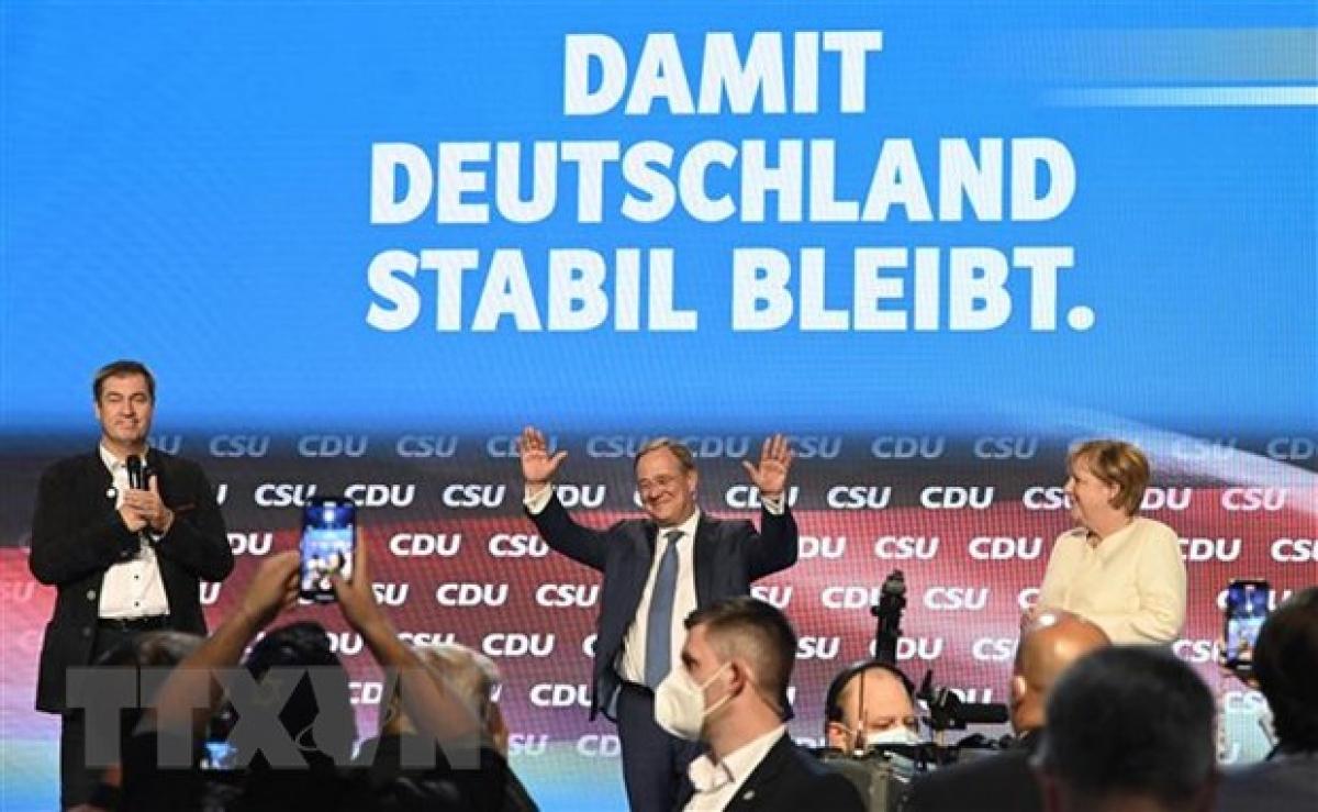 Thủ tướng Đức Angela Merkel (phải) và ứng cử viên Thủ tướng của liên minh CDU/CSU Armin Laschet (giữa) tại cuộc vận động tranh cử ở Munich, Đức, ngày 24/9. (Ảnh: AFP/TTXVN)