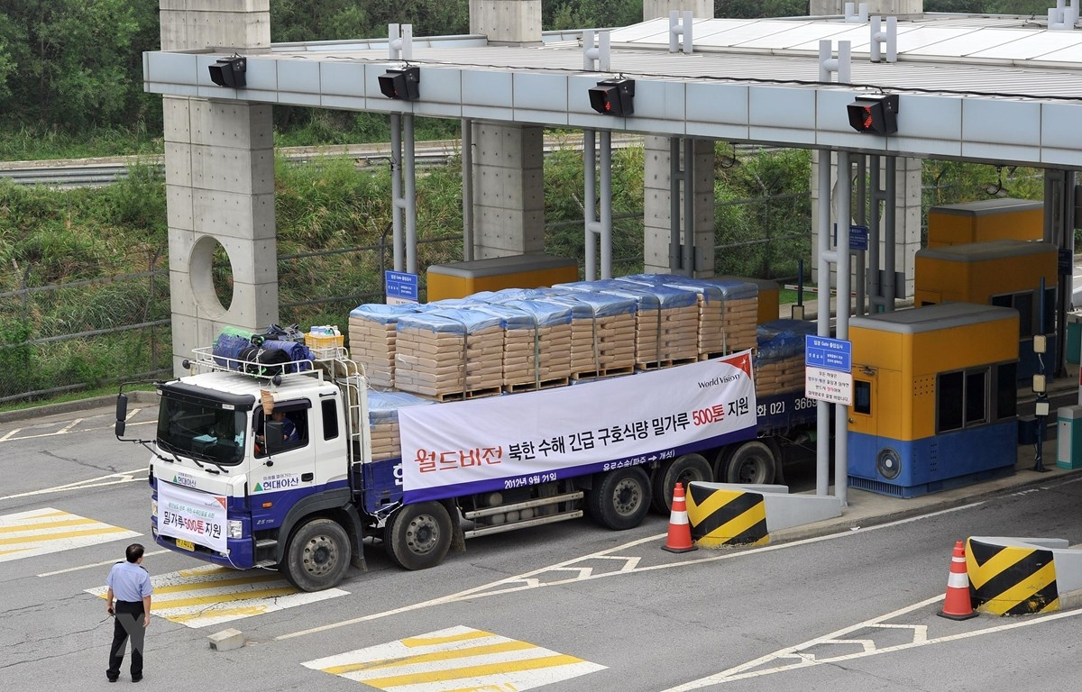 Xe tải của Hàn Quốc chở bột mì viện trợ cho Triều Tiên qua cửa khẩu biên giới tỉnh Paju. (Ảnh: AFP/TTXVN)