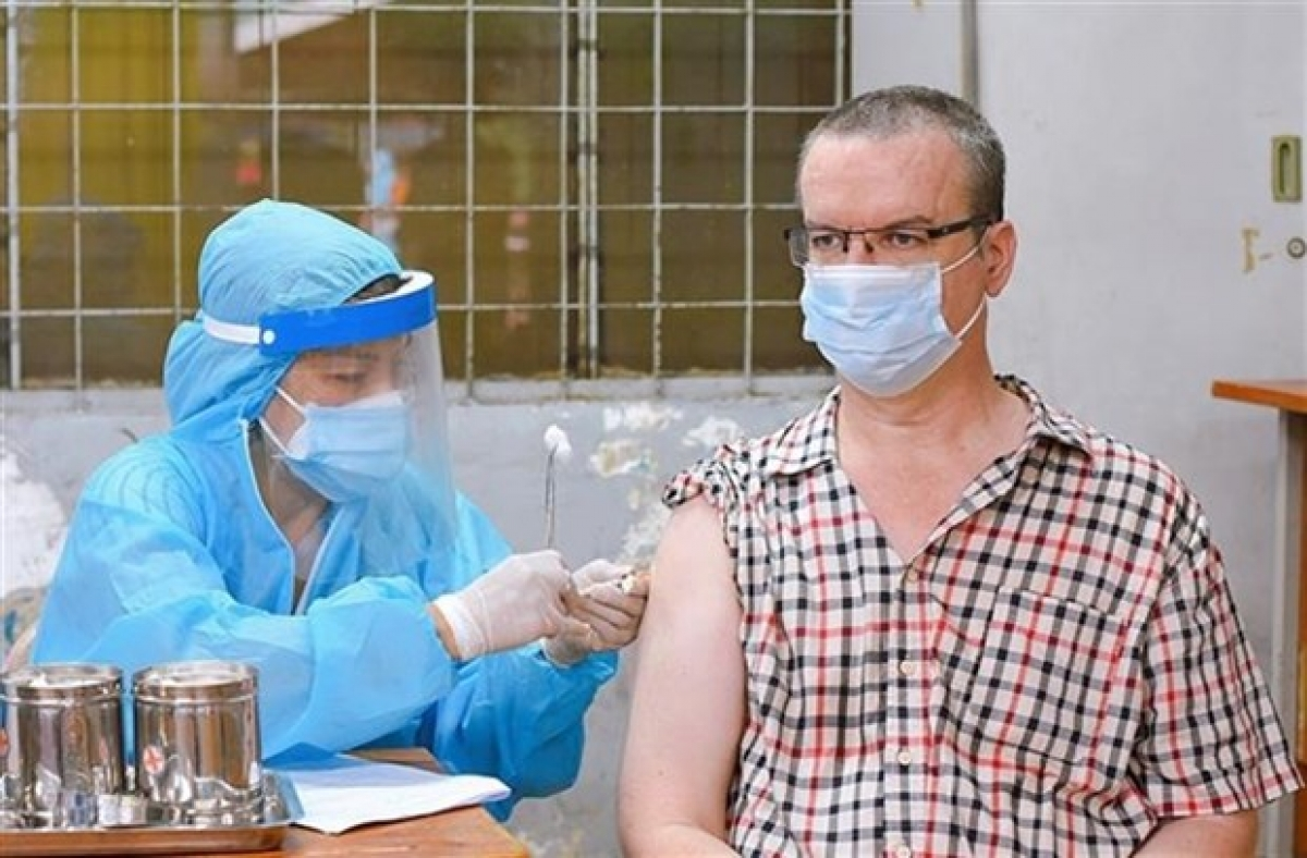 A foreigner gets vaccinated against COVID-19 in HCM City