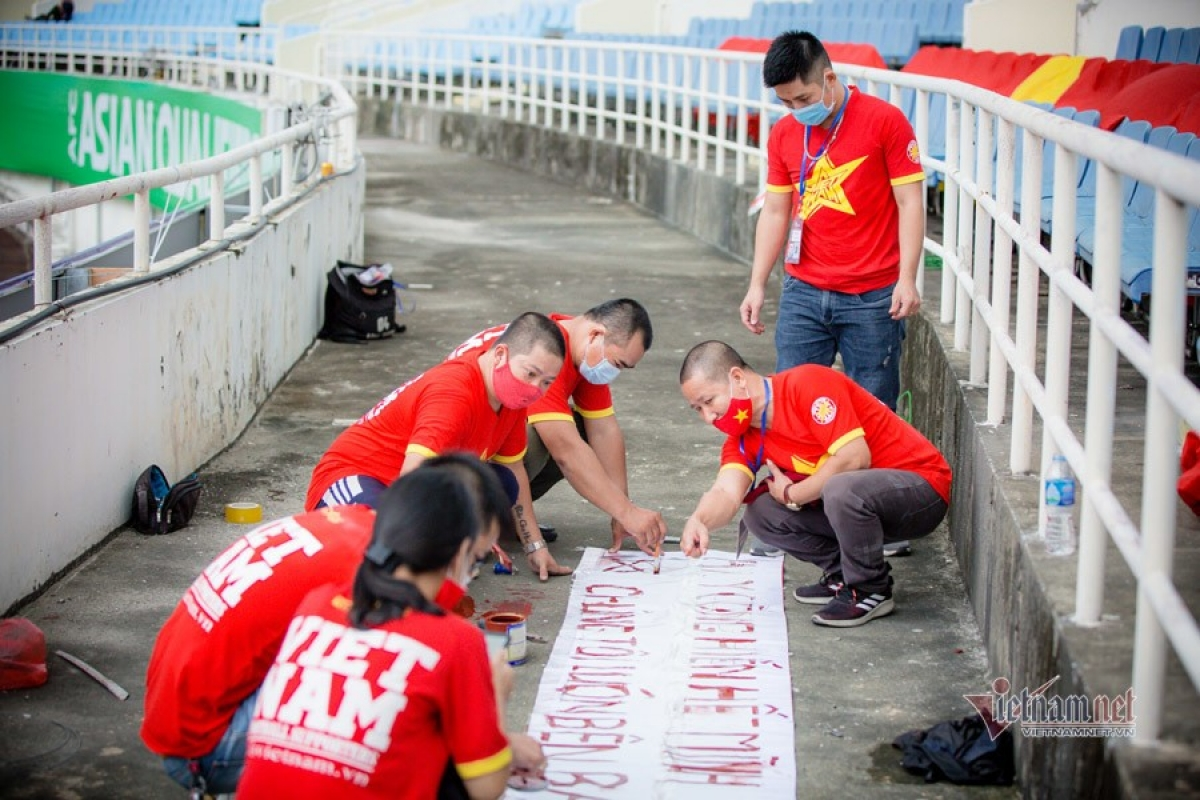 Fans paint words on their banners to support the team.