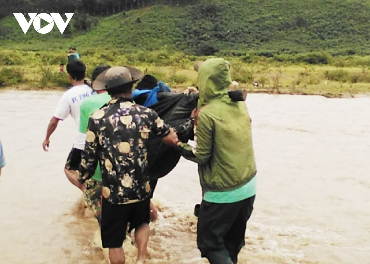 Rescue workers retrieve the body of a woman washed away by violent floodwaters in Tu Mo Rong district, Kon Tum province.
