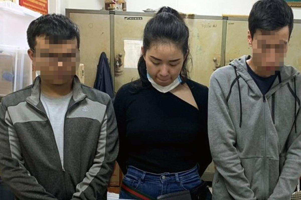 Lê Thùy Trang (giữa) sau khi bị bắt. (Ảnh: Công an Hà Nội)