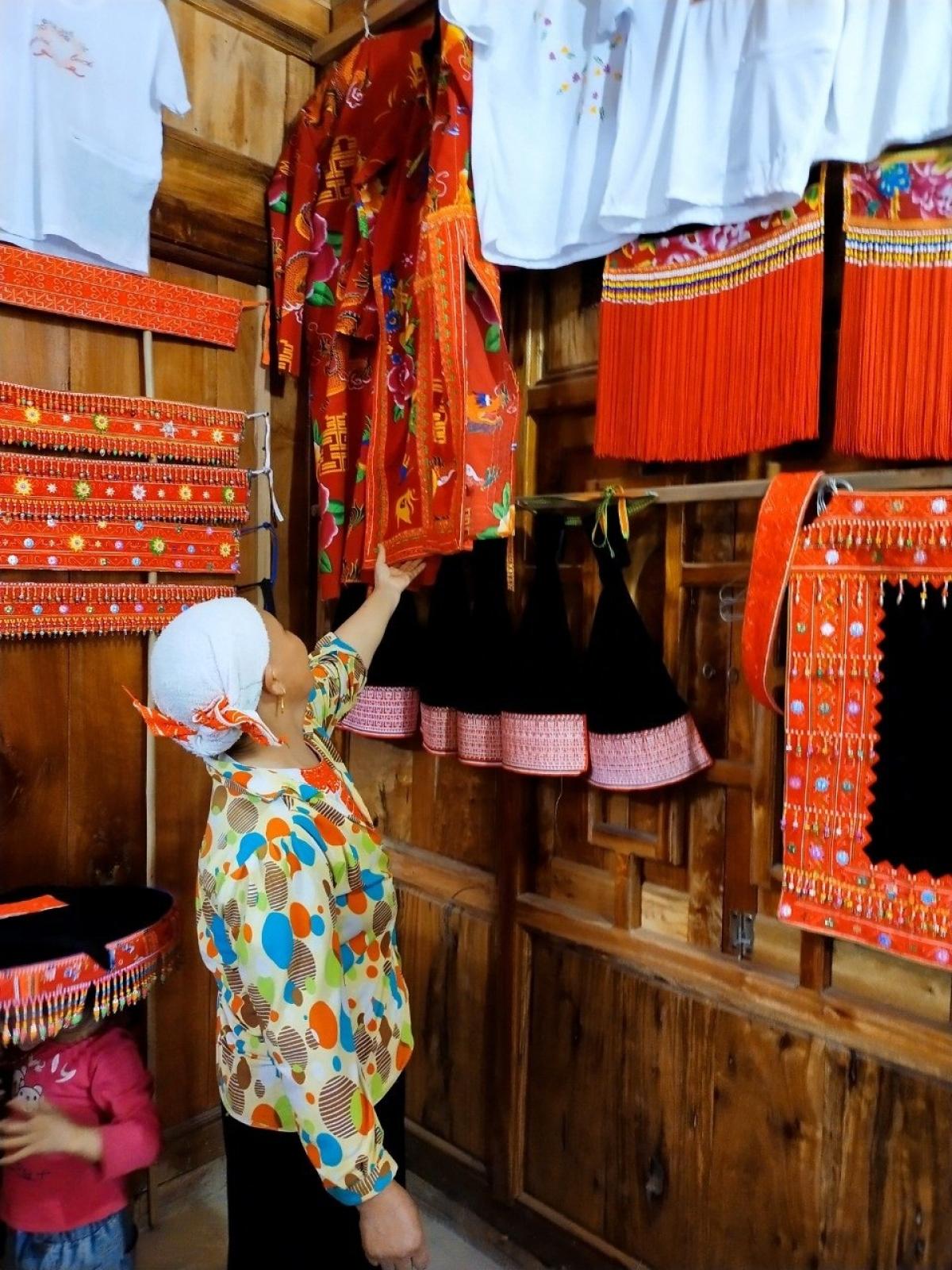 Bà Lý Mùi Lai giới thiệu lễ phục với họa tiết sặc sỡ trong lễ cấp sắc.Ảnh: Hồng Son