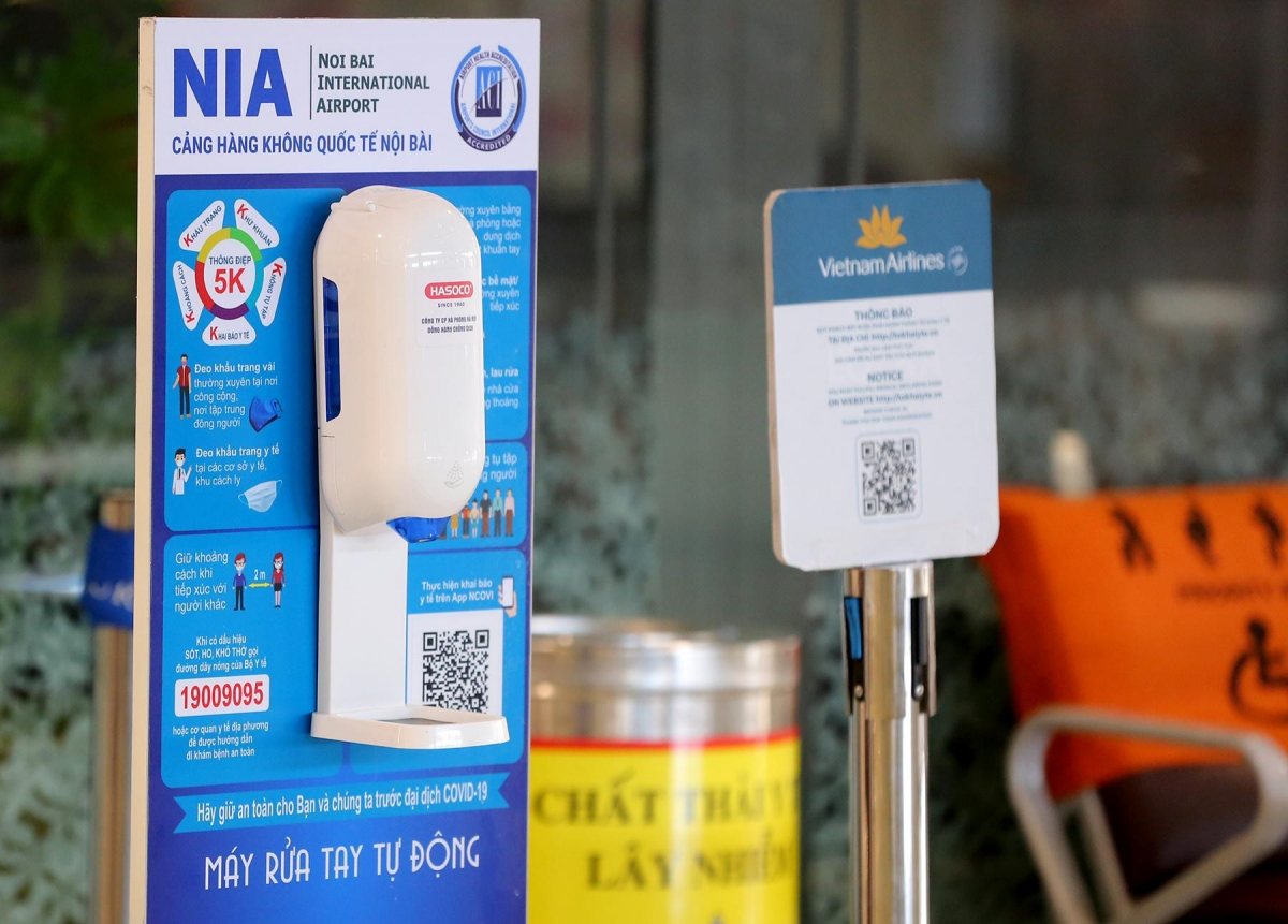 Guidance to follow the Health Ministry's 5K message, QR code scanning for healthcare declaration, and bottles of hand sanitizer are placed throughout Noi Bai Airport.