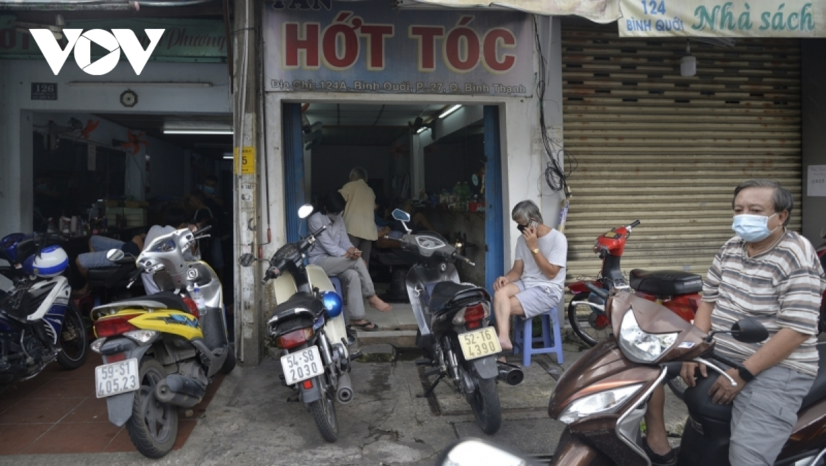 Residents patiently wait their turn at a barber shop in Binh Thanh district.