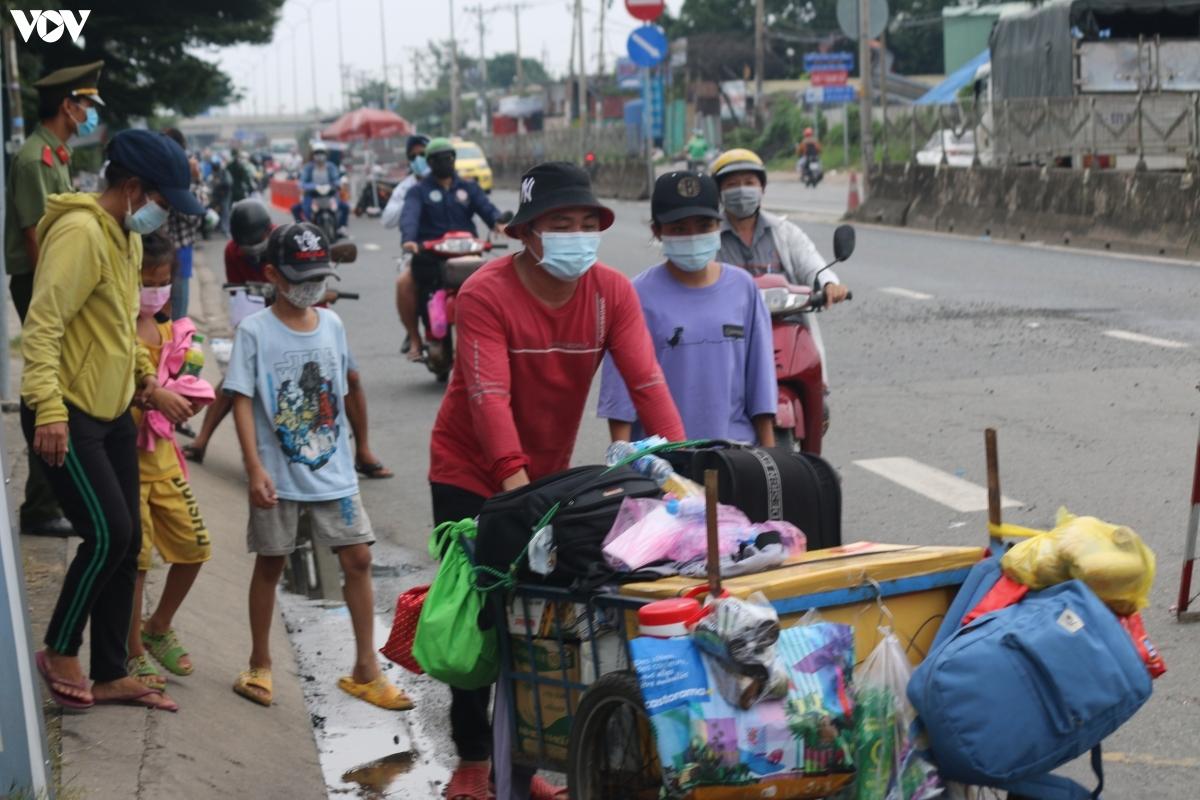 Một gia đình đi bộ, đẩy xe chất đầy hành lý về quê.