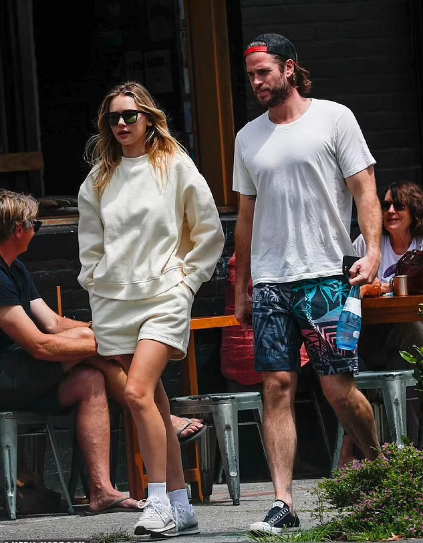 Cặp đôi mặc đồ giản dị, thoải mái trò chuyện khi đang sải bước trên phố.