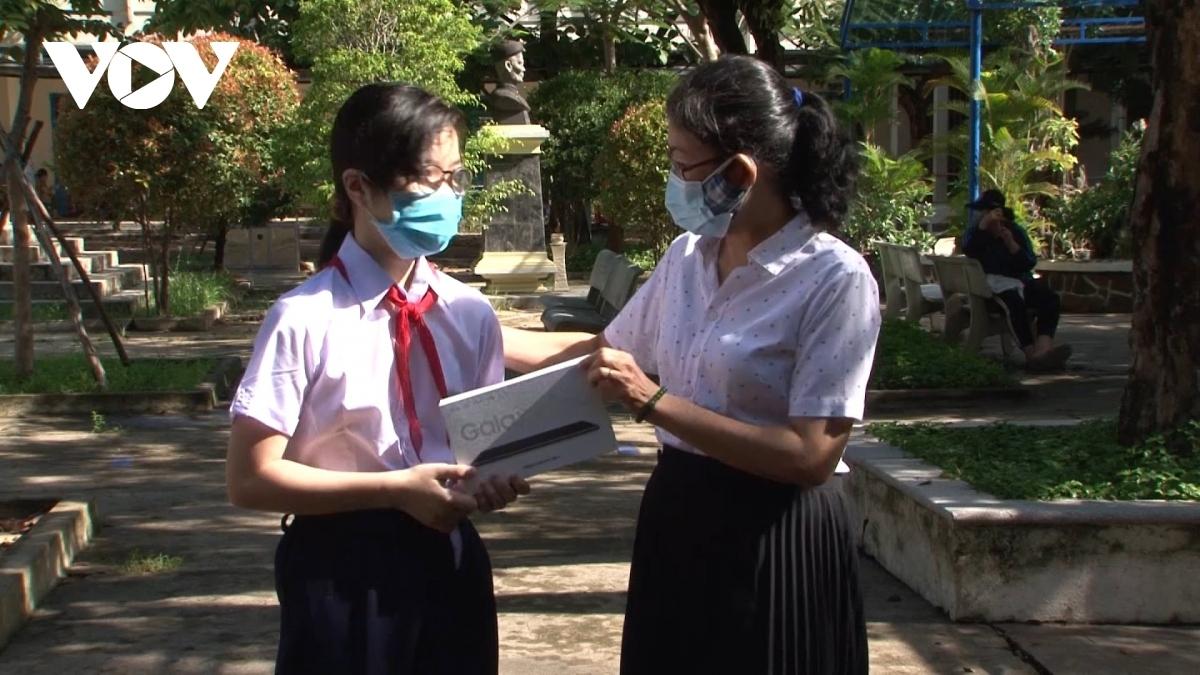 Cô Nguyễn Thị An (bên phải), Hiệu trưởng Trường THCS Huỳnh Thúc Kháng, quận Thanh Khê, Đà Nẵng trao tận tay học sinh hoàn cảnh khó khăn chiếc máy tính bảng.