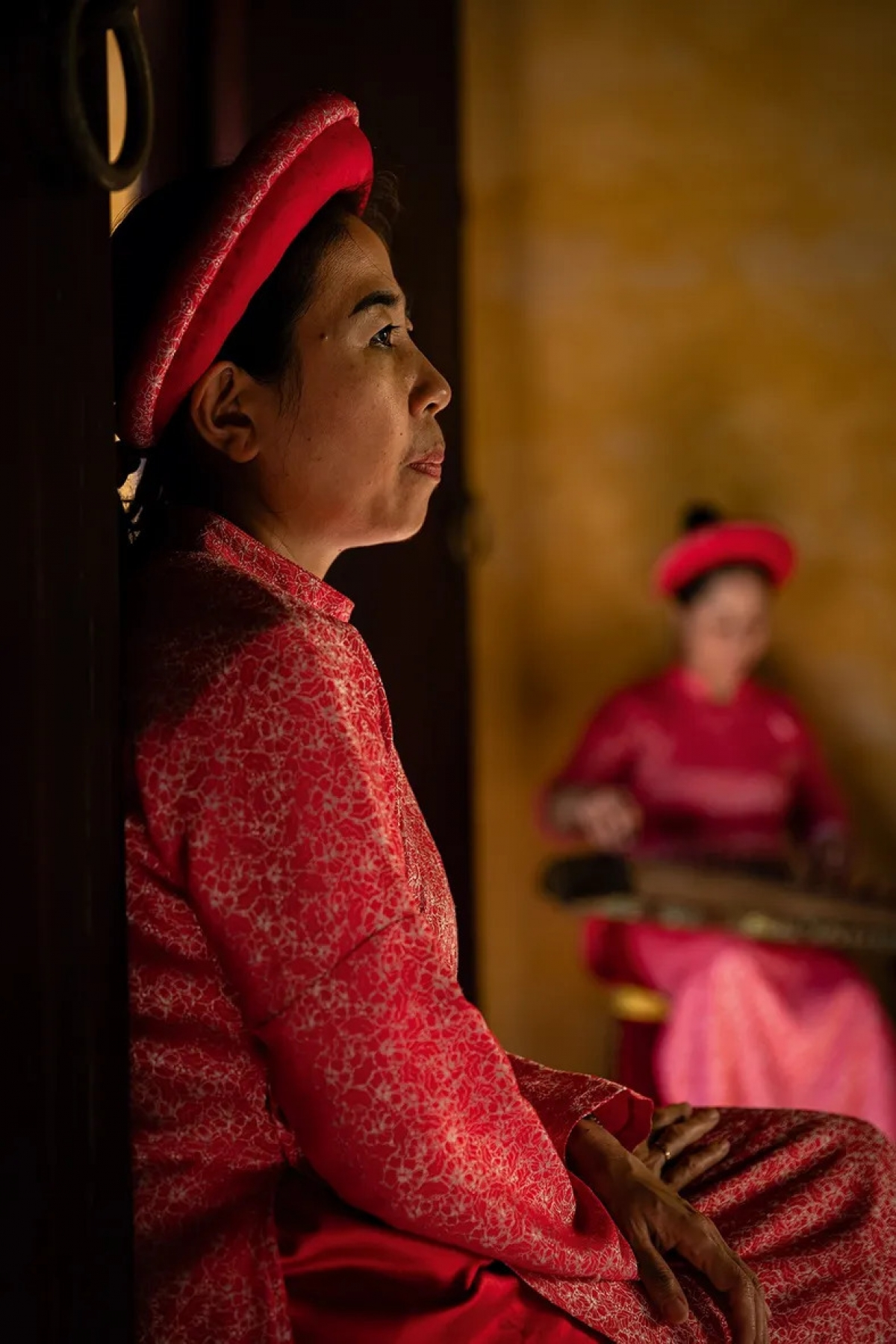 Vietnamese woman in traditional clothing in the Imperial City of Hue by Walter Monticelli.