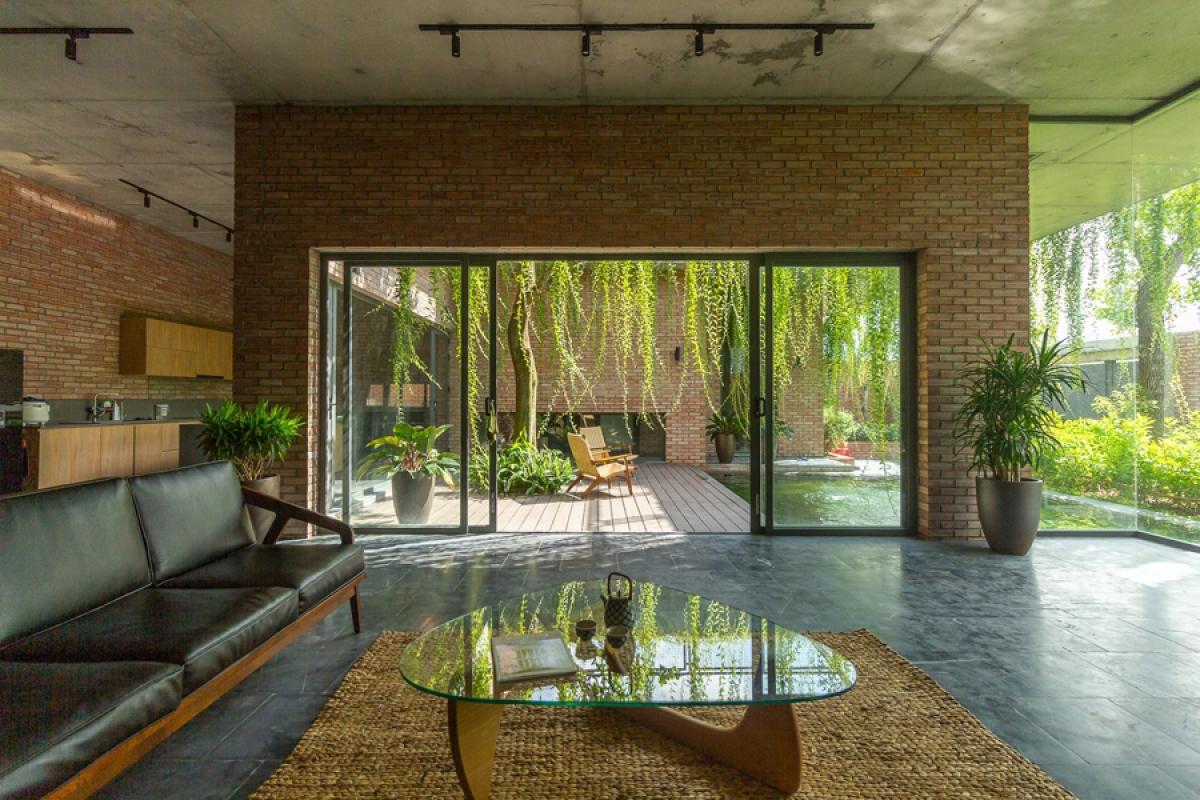Phòng khách mở ra khoảng vườn phía trước nhà và khoảng sân trung tâm. Nhờ những ô cửa kính lớn nên ánh sáng tự nhiên luôn chan hòa.
