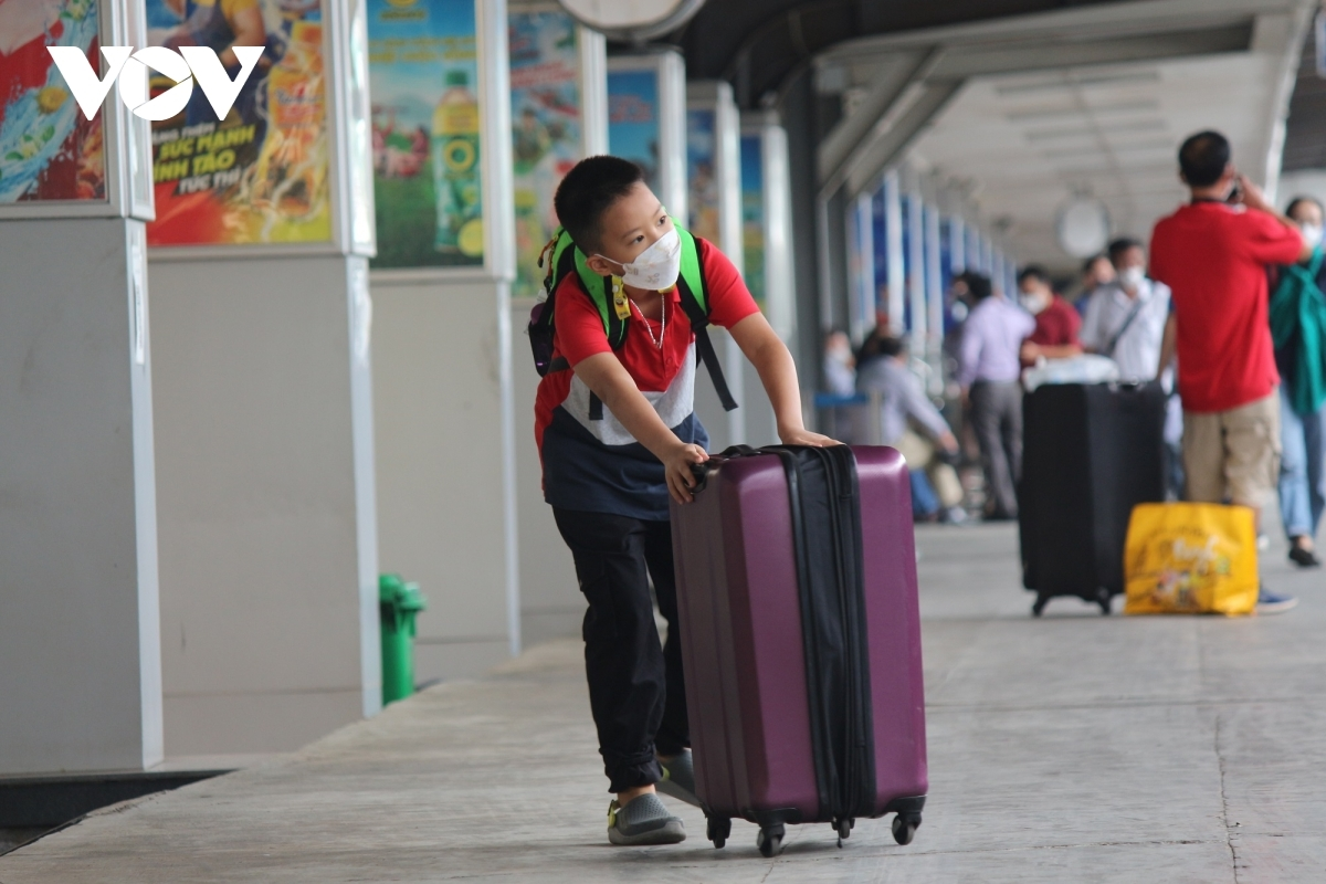Children join their families as they head back to their hometown after several months being left stranded in Hanoi.