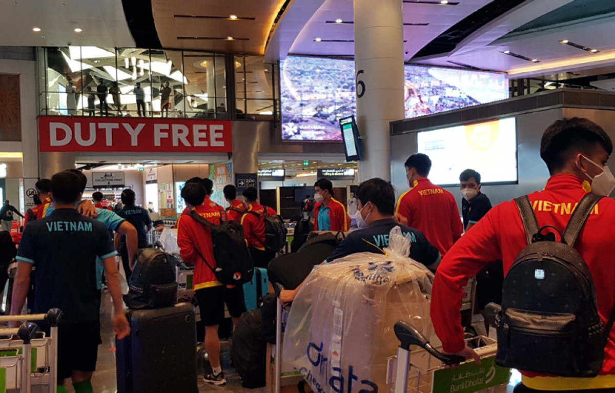 The players carry their hand luggage to the boarding gate.