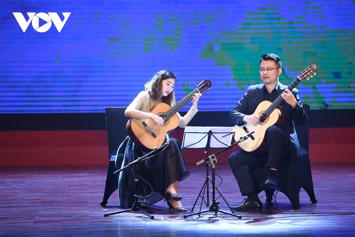 """Mở màn chương trình, hai nghệ sĩ guitar Vũ Đức Hiển và Thang Thị Bích Hằng biểu diễn 2 bản nhạc  """"Oblivion """" và  """"Milonga """" của các nhà soạn nhạc người Argentina Astor Piazzolla và Jorge Cardoso."""