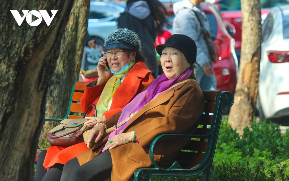 """Trời ấm lên, người Hà Nội tranh thủ """"sưởi nắng"""" bên hồ Hoàn Kiếm - Ảnh 4."""