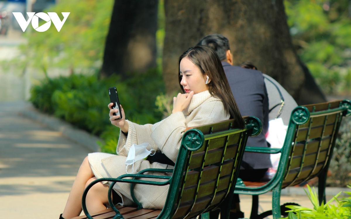 """Trời ấm lên, người Hà Nội tranh thủ """"sưởi nắng"""" bên hồ Hoàn Kiếm - Ảnh 6."""